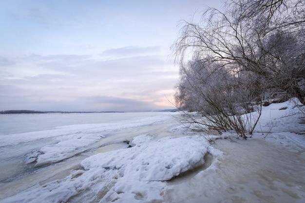 Paesaggio invernale all'alba, riva di un ghiaccio ghiacciato.