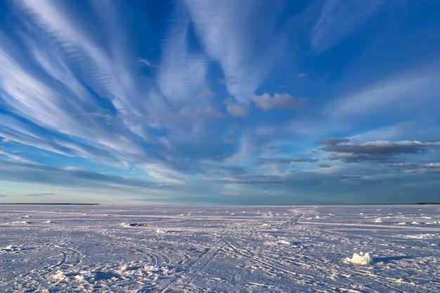 Paesaggio invernale con fiume nel ghiaccio e neve con cielo blu e nuvole bianche