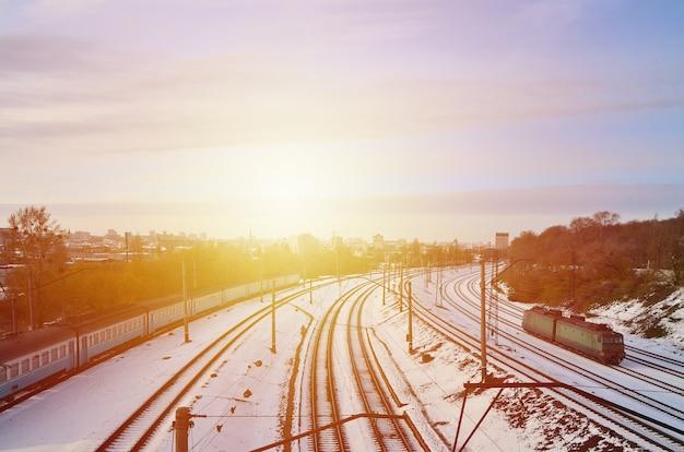Paesaggio invernale con un treno ferroviario su uno sfondo di cielo nuvoloso