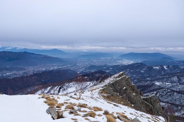 Paesaggio invernale, valle alpina e catena montuosa innevata, nuvole nuvolose scure.