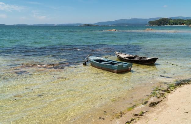 Paesaggio marino di rias baixas, in galizia, con due piccole imbarcazioni chiamate chalanas