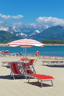 Paesaggio marino italiano spiaggia, mare e montagna. stabilimento balneare.