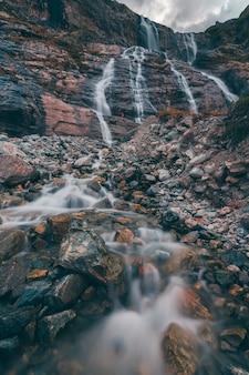 Paesaggio montano, cascata in sfocatura dal basso