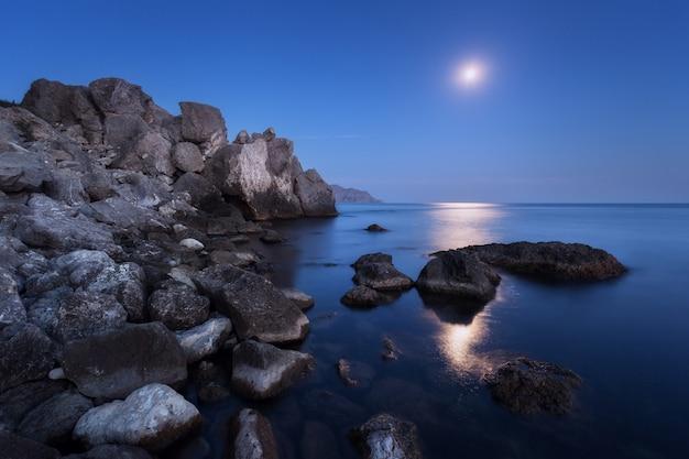 Paesaggio notturno colorato con luna piena, percorso lunare e rocce in estate