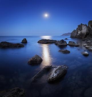 Paesaggio notturno con la luna piena, percorso lunare e rocce in estate