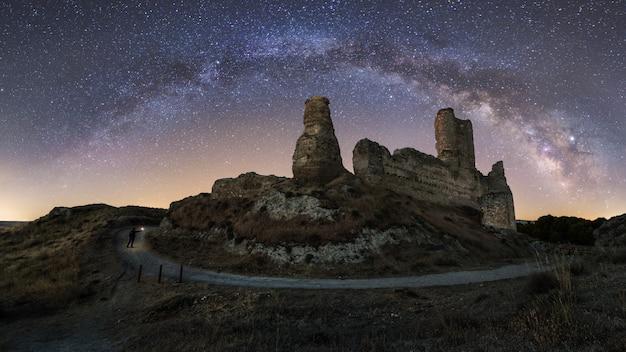 Paesaggio notturno con la via lattea sopra un vecchio castello