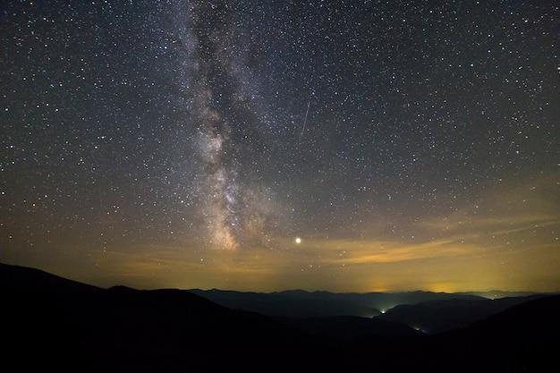 Paesaggio notturno delle montagne con cielo coperto di stelle.