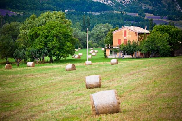 Paesaggio rurale con fattoria e balle di paglia