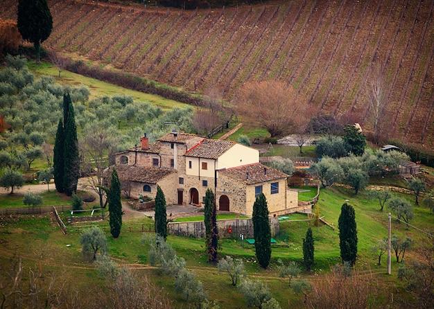 Paesaggio toscano con cipressi, alberi e antichi edifici.