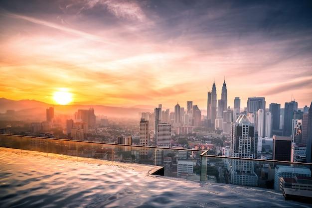 Paesaggio urbano dell'orizzonte della città di kuala lumpur con la piscina sulla cima del tetto dell'hotel all'alba in malesia.