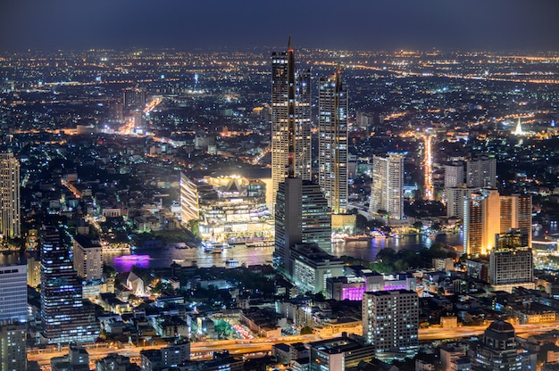 Paesaggio urbano della costruzione illuminata con il grande magazzino vicino al fiume di chao phraya