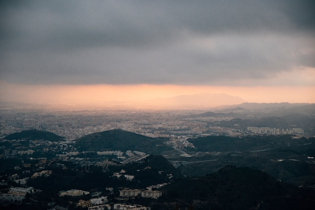 Paesaggio urbano e montagna sotto le nuvole tempestose
