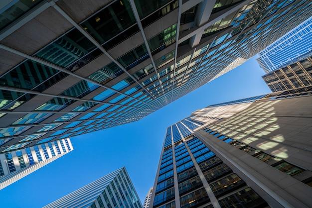 Paesaggio urbano moderno delle costruzioni di vetro dell'ufficio sotto il chiaro cielo blu a washington dc, usa, architettura simmetrica e di prospettiva del grattacielo finanziario all'aperto