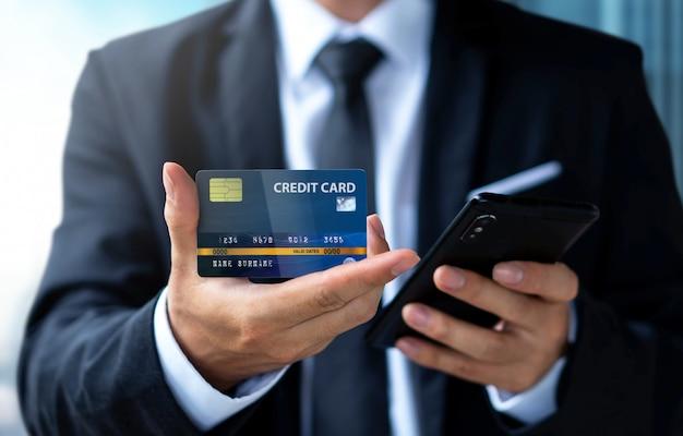 Paga dell'uomo d'affari o acquistando dalla carta di credito con lo smartphone
