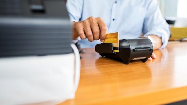 Pagamenti con carta tra uomini d'affari tramite macchina con carta di credito in ufficio.