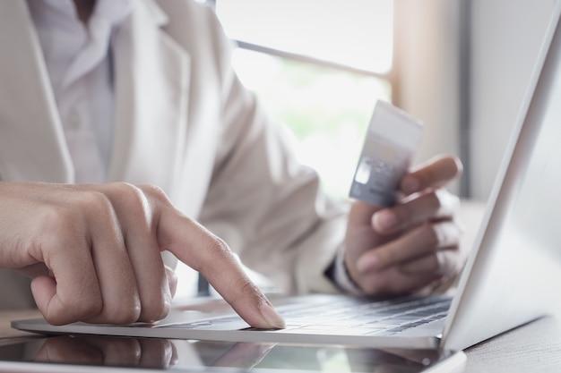 Pagamento online, la mano del giovane che utilizza il computer portatile e la carta di credito della tenuta della mano per lo shopping online.