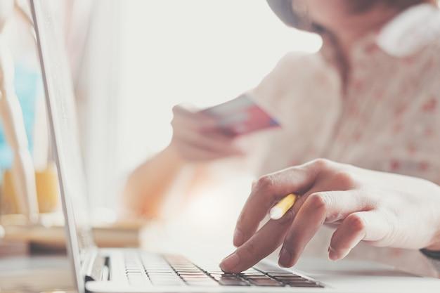 Pagamento online, le mani della donna di affari che tengono una carta di credito e che utilizzano computer portatile per lo shopping online.