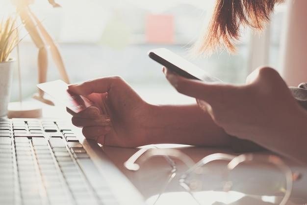 Pagamento online, le mani della giovane donna tramite smartphone e la mano che tiene la carta di credito per lo shopping online