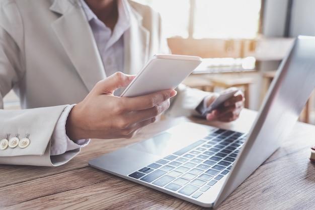 Pagamento online, mani del giovane che tengono smart phone mobile e carta di credito con l'utilizzo del computer portatile per lo shopping online.