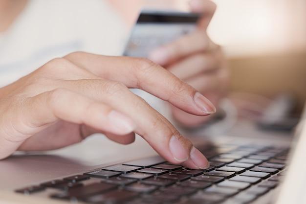 Pagamento online, mani del giovane tramite carta di credito e computer portatile per lo shopping online