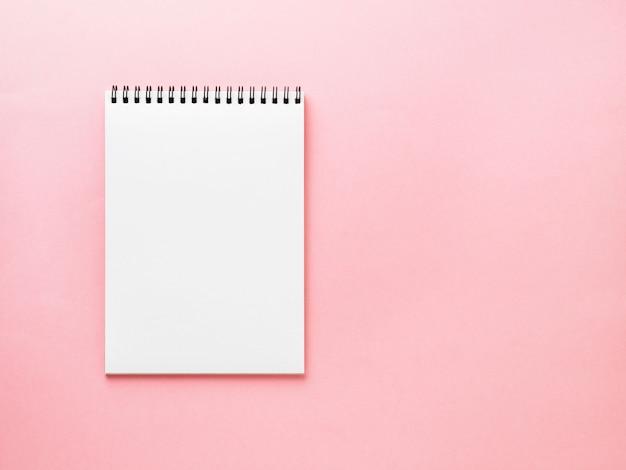 Pagina bianca del blocco note in bianco sullo scrittorio rosa, fondo di colore. vista dall'alto, vuota per il testo.