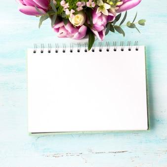 Pagina bianca del taccuino in bianco con i fiori rosa porpora