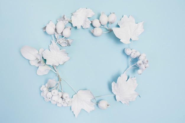 Pagina con le foglie bianche sul modello di disposizione del piano del backgound blu per il vostro spazio della copia della composizione in autunno dell'iscrizione di arte, dell'immagine o della mano, vista superiore