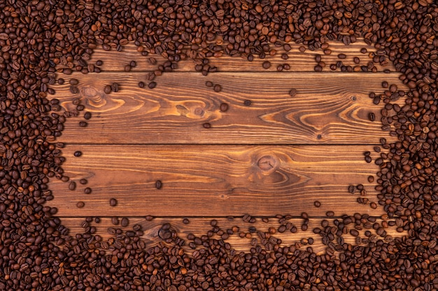 Pagina dei chicchi di caffè sulla tavola di legno marrone