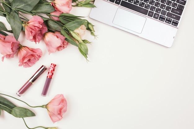Pagina dei cosmetici e dei gioielli delle donne decorative con i fiori di eustoma, vista superiore. disposizione floreale piana di disposizione sulla parete bianca