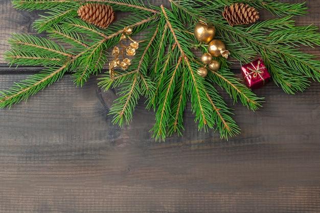Pagina dei rami e delle palle dell'abete su un fondo di legno rustico scuro