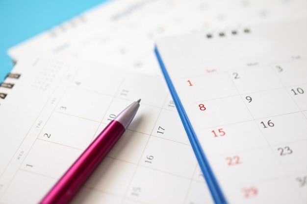 Pagina del calendario con la penna si chiuda sul concetto di riunione appuntamento appuntamento di pianificazione aziendale sfondo blu