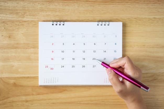 Pagina del calendario sul tavolo con mano femminile che tiene la penna