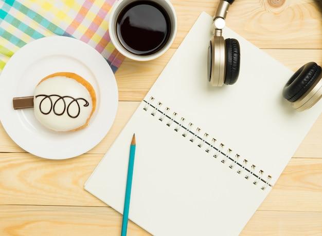 Pagina del libro in bianco sulla tavola di legno del caffè pastello variopinto