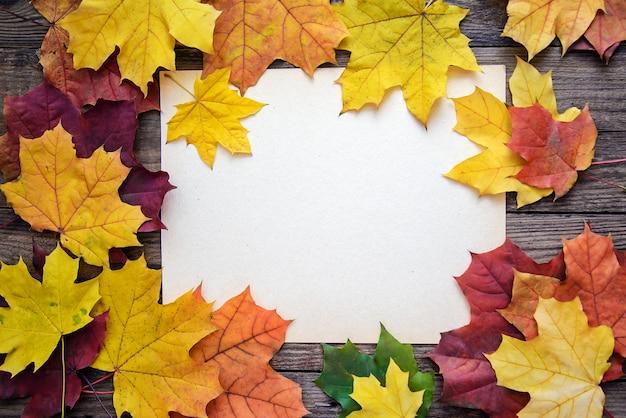 Pagina delle foglie di autunno e un foglio di carta bianco su un fondo di legno della plancia