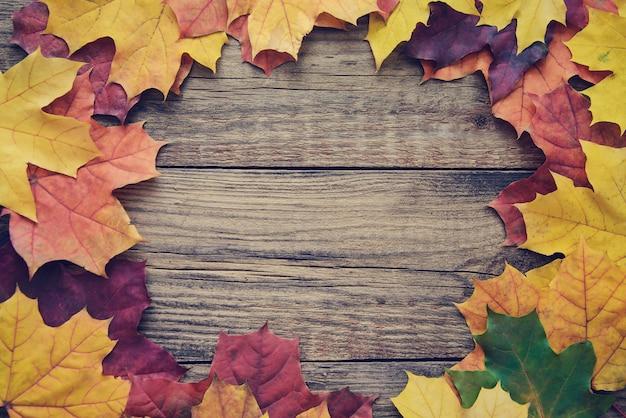 Pagina delle foglie di autunno su fondo di legno