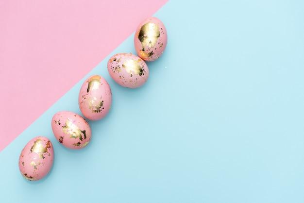 Pagina delle uova decorate dorate di pasqua sul fondo di rosa pastello.