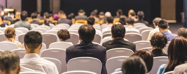 Pagina di copertina dello striscione di vista posteriore dell'udienza del pubblico altoparlanti sul palco nella sala delle conferenze