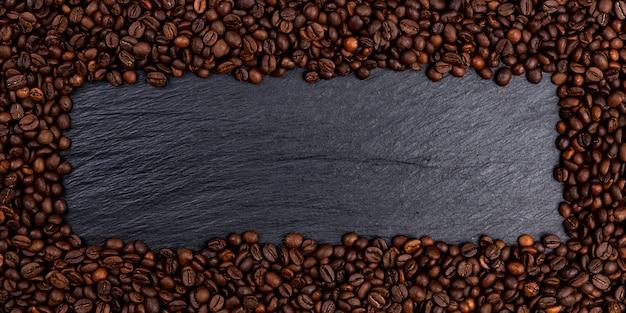 Pagina fatta dei chicchi di caffè arrostiti sulla tavola nera