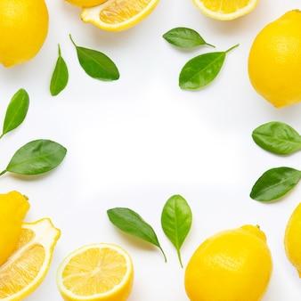 Pagina fatta del limone e delle fette freschi con le foglie isolate su bianco