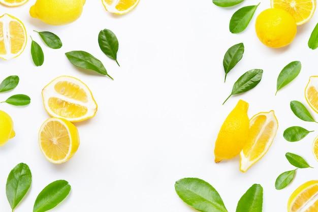 Pagina fatta del limone fresco con le foglie verdi su bianco.