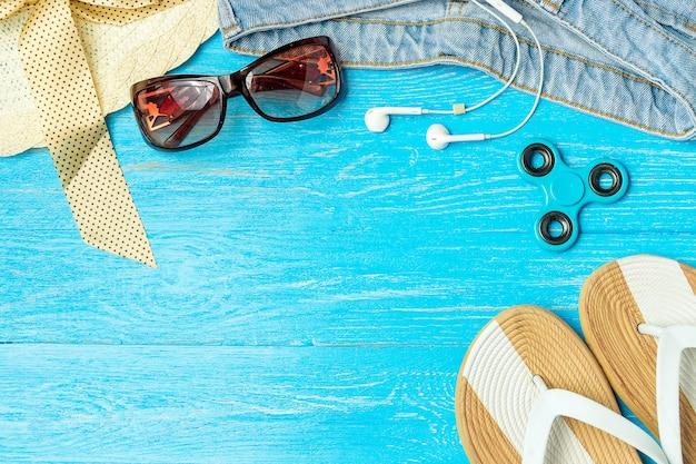 Pagina gli occhiali da sole femminili eleganti dei jeans delle pantofole del cappello di paglia su fondo di legno blu, copyspace per testo, vacanze estive.