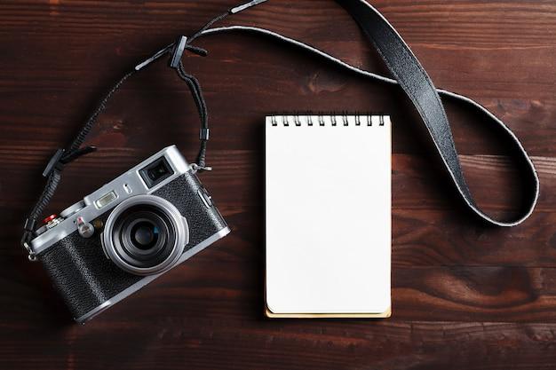 Pagina in bianco del blocco note e macchina fotografica moderna nello stile classico sulla tavola di legno di marrone scuro