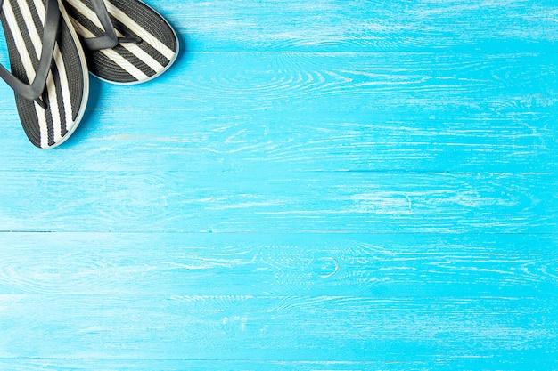 Pagina le pantofole femminili eleganti su fondo di legno blu, copyspace per testo, vacanze estive.