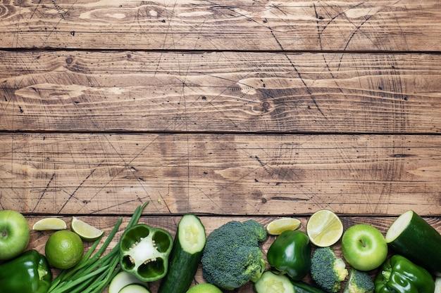Pagina verdure ed erbe verdi fresche su un fondo di legno. copia spazio.