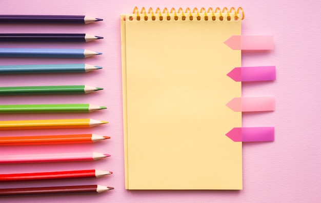 Pagina vuota del rilievo di schizzo a spirale verticale con i pastelli sul colore rosa