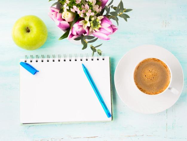 Pagina vuota del taccuino con i fiori blu del caffè della tazza e della penna