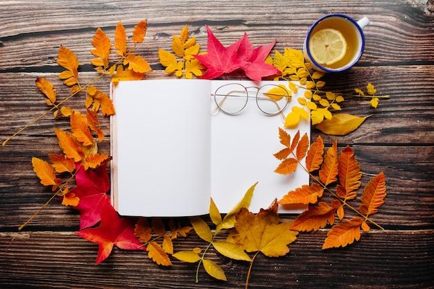 Pagine del blocco note in bianco del giornale della pallottola in uno spazio accogliente con la tazza dello smalto del tè dello zenzero del limone, i vetri e le foglie di autunno rosse, arancio e gialle variopinte su una tavola di legno.