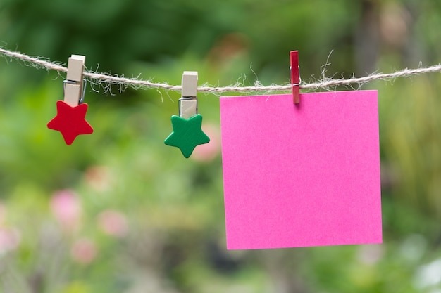 Pagine del blocco note quadrate vuote e la graffetta. carta per appunti attaccata con una graffetta.