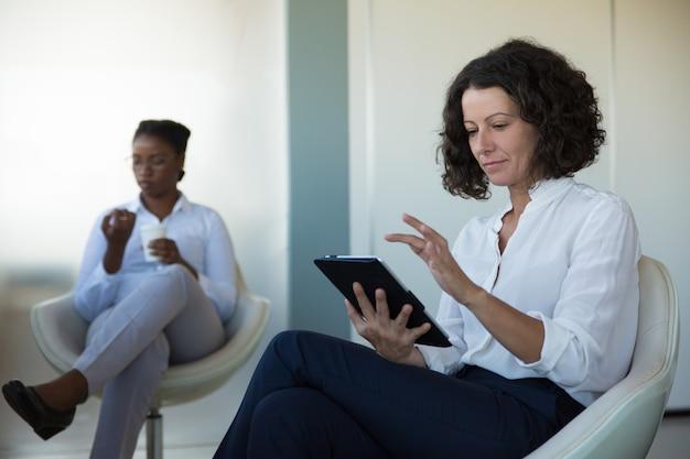 Pagine di ricerca della donna di affari sul tablet nel salotto dell'ufficio