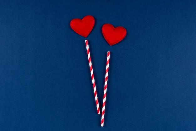 Paglia di carta rossa con cuore su sfondo blu classico colore 2020. san valentino 14 febbraio concetto. vista piana, copia spazio, vista dall'alto.